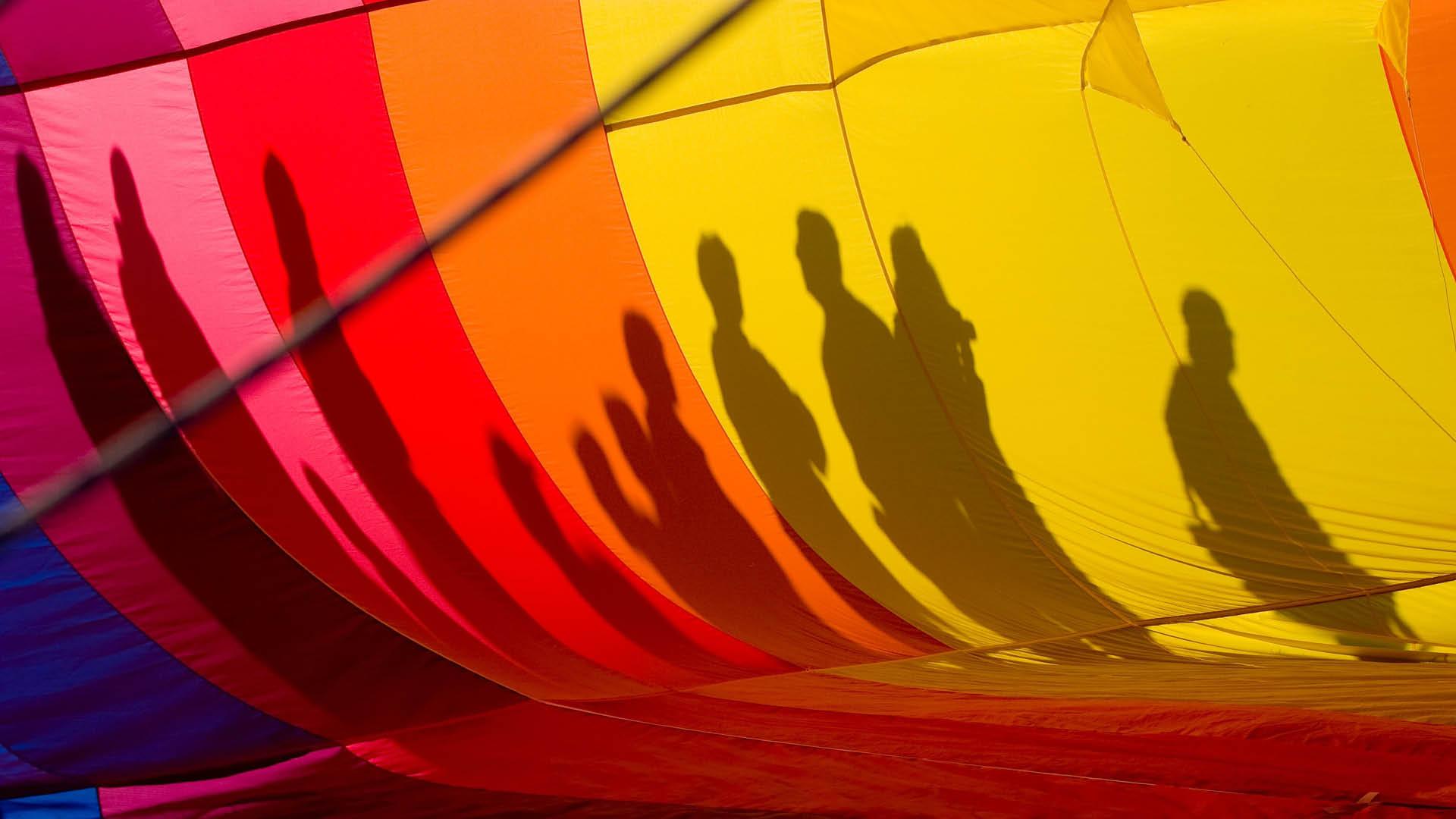 Regnbueflag med skygger af personer